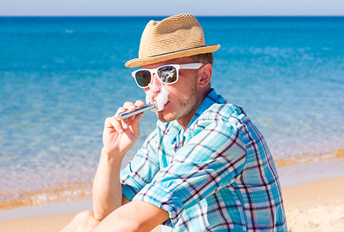 Vaping around the world hipster on a beach travel vape